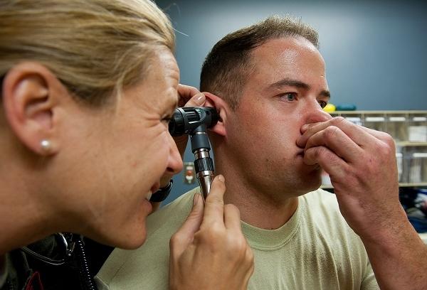 Klassisches Valsalva Manöver bei einer medizinischen Untersuchung beim Militär zur Evaluation der Hörfähigkeit des Probanden.